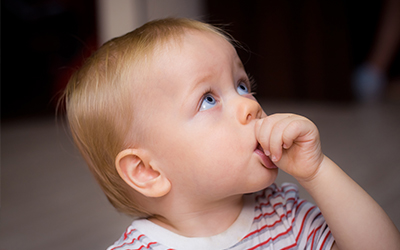 A young child sucking their thumb