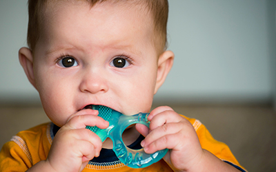 A toddler chewing on a teething toy