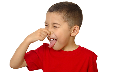 A young boy plugging his nose