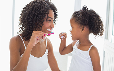 young girl and mother brushing teeth together