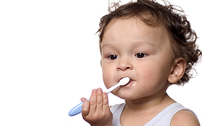 A toddler brushing their teeth