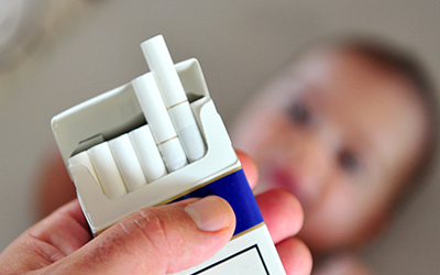 a person holding a pack of cigarettes with a baby in the background