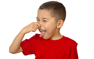 A young boy plugging his nose and sticking his tongue out